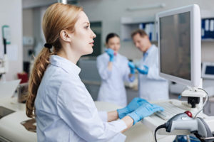 female doctor typing on computer in lab